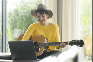 Portrait of smiling woman sitting on couch with guitar looking at laptop - SBOF01845