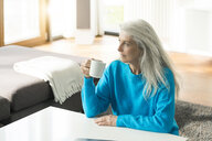 Pensive mature woman with cup of coffee at home looking at distance - SBOF01848