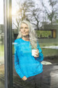 Portrait of content mature woman with cup of coffee leaning against terrace door looking at distance - SBOF01851