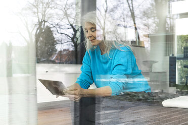Portrait of smiling mature woman sitting on the couch at home looking at digital tablet - SBOF01854