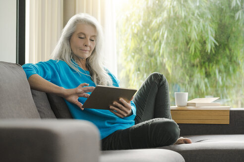 Portrait of mature woman sitting on the couch at home using digital tablet - SBOF01857