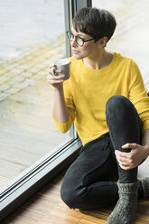 Woman with cup of coffee sitting on the floor at home looking out of window - SBOF01863