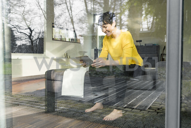 Laughing woman sitting behind windowpane on couch in the living room looking at digital tablet - SBOF01869 - Steve Brookland/Westend61