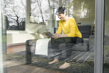 Laughing woman sitting behind windowpane on couch in the living room looking at digital tablet - SBOF01869