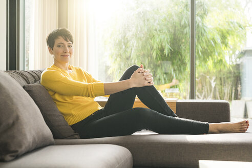 Portrait of smiling woman relaxing on the couch at home - SBOF01872