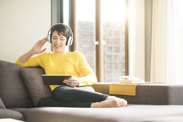 Portrait of happy woman sitting on the couch at home listening music with headphones while looking at tablet - SBOF01875