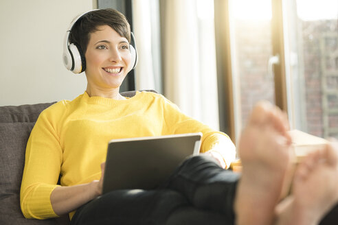 Portrait of happy woman with headphones and digital tablet sitting on the couch at home - SBOF01878