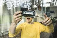 Portrait of amazed woman behind windowpane using Virtual Reality Glasses - SBOF01881