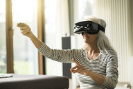 MAture woman using Virtual Reality Glasses at home - SBOF01884
