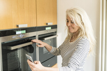 Content mature woman with smartphone checking oven in kitchen of her smart home - SBOF01887