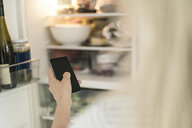 Hand of woman with smartphone checking fridge in kitchen at smart home - SBOF01890
