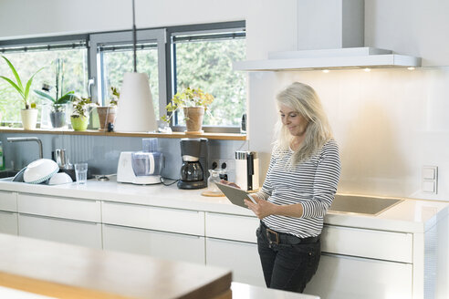 Content woman standing in kitchen using digital tablet - SBOF01893