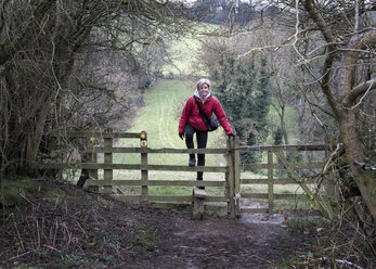 UK, Gloucester, Chipping Sodbury, Cotswold Way, woman on a hiking trip crossing pasture fence - ALRF01414