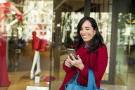 Happy woman using cell phone in front of shop window - VABF02234