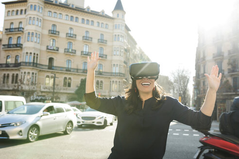 Excited woman wearing VR glasses in the city - VABF02249