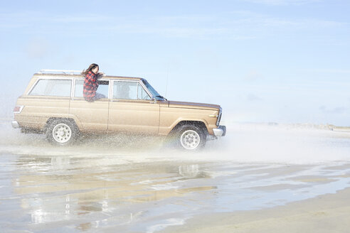 Germany, St Peter-Ording, girl leaning out of window of off-road vehicle driving through water on the beach - AMEF00033