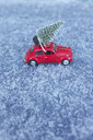 Red vw beetle toy car with Christmas tree on roof in snowy conditions - GISF00400