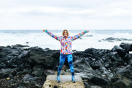 Portugal, Azores Islands, Sao Miguel, Woman with arms raised with the sea in the background in rocky landscape - KIJF02411