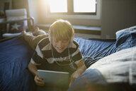 Boy with headphones using digital tablet on bed - HEROF26932