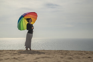 Woman with colorful umbrella standing at the beach - KBF00550