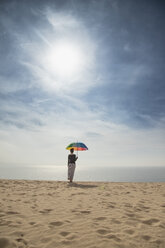 Woman with colorful umbrella standing at the beach, rear view - KBF00553