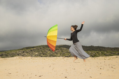 Woman holding colorful umbrella on a dune - KBF00556