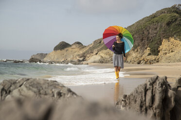Woman with colorful umbrella walking on the beach - KBF00559