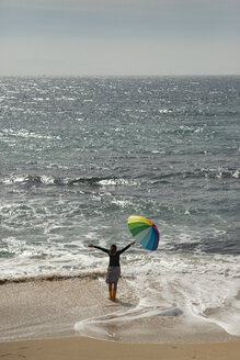 Woman with colorful umbrella standing on the beach, raised arms - KBF00562