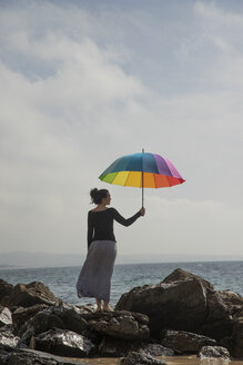 Woman holding colorful umbrella on rocky beach, rear view - KBF00565
