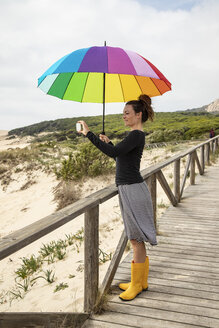 Woman with colorful umbrella standing on the beach, taking a selfie - KBF00568