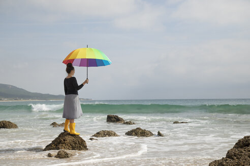 Woman with colorful umbrella standing on a stone at the beach - KBF00571