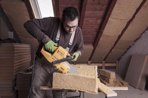 Roof insulation, worker cutting wood fibre insulation - SEBF00023