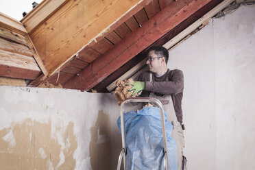 Roof insulation, worker placing woodfibre insulation - SEBF00026