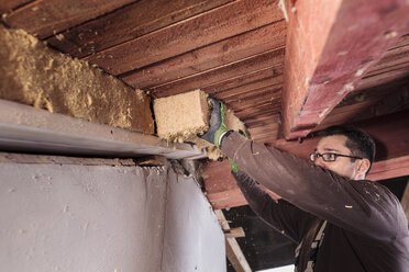 Roof insulation, worker filling pitched roof with wood fibre insulation - SEBF00029