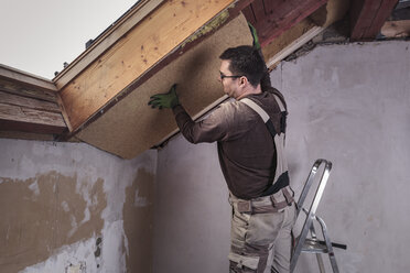 Roof insulation, worker placing insulating board, wood fibre - SEBF00032