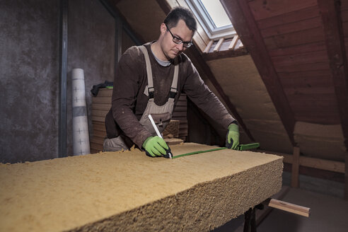Roof insulation, worker measuring wood fibre insulation - SEBF00035