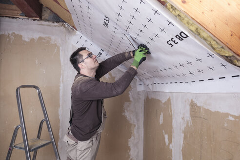 Roof insulation, worker fixing sarking membrane - SEBF00038