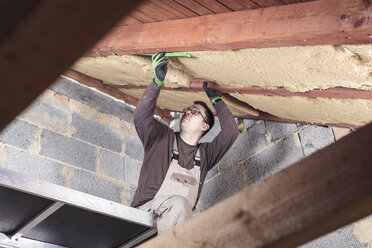 Roof insulation, worker filling pitched roof with wood fibre insulation - SEBF00041