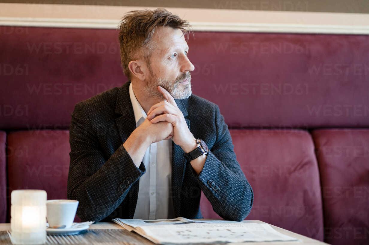 Pensive mature businessman with newspaper in a coffee shop - DIGF06006 - Daniel Ingold/Westend61
