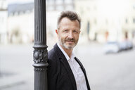Portrait of mature businessman with greying beard leaning against lamp pole - DIGF06012