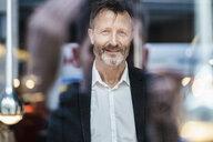 Portrait of smiling mature businessman behind windowpane - DIGF06015