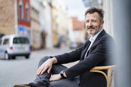 Portrait of content mature businessman with greying beard sitting on chair in the city - DIGF06024