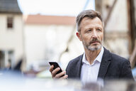 Portrait of mature businessman with mobile phone watching something - DIGF06030