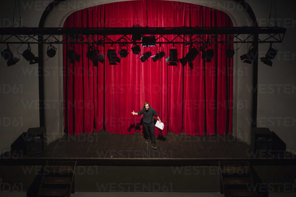 Rehearsing actor with script standing on theatre stage in front of red curtain - FBAF00249 - Francesco Buttitta/Westend61