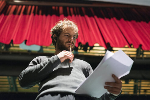 Portrait of pensive man standing on stage of theatre looking at script - FBAF00258