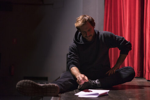 Actor sitting on stage of theatre looking at script - FBAF00270