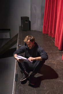 Rehearsing actor sitting on stage of theatre looking at script - FBAF00273