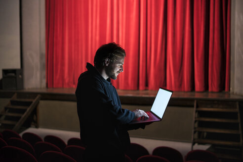 Director standing at auditorium of theatre using laptop - FBAF00285