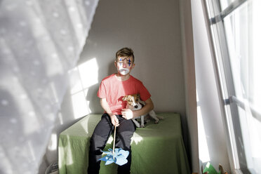 Portrait of boy made up as a clown with dog and pin wheel at home - KMKF00781