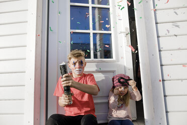 Brother and little sister made up for carnival sitting in front of entry door - KMKF00787